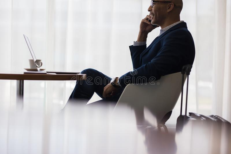 Business traveler making a phone call from airport lounge. Businessman sitting at airport lounge and talking on cell phone. Male business traveler sitting at royalty free stock photos