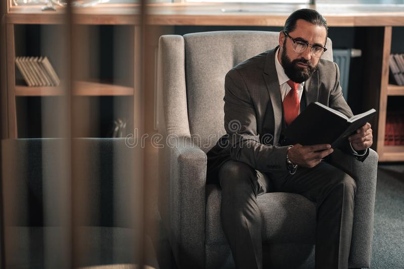 Businessman sitting in armchair feeling involved in reading stock photography
