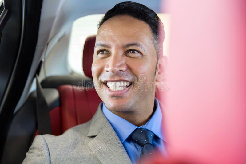 Businessman sitting backseat. Handsome middle aged businessman sitting on the backseat in a car royalty free stock image