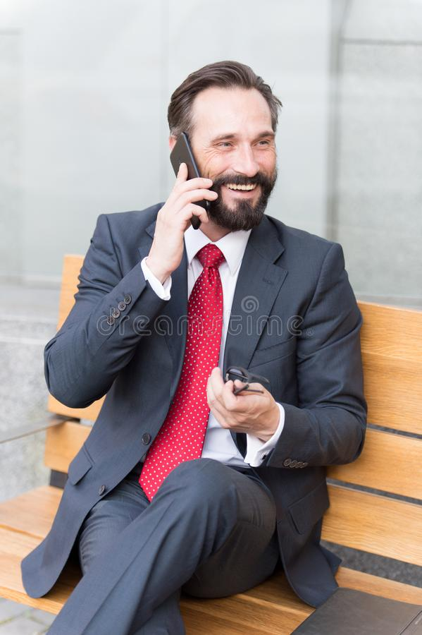 Businessman sitting on bench using his cell phone. Smiling bearded businessman sitting on bench and talking on the phone royalty free stock images