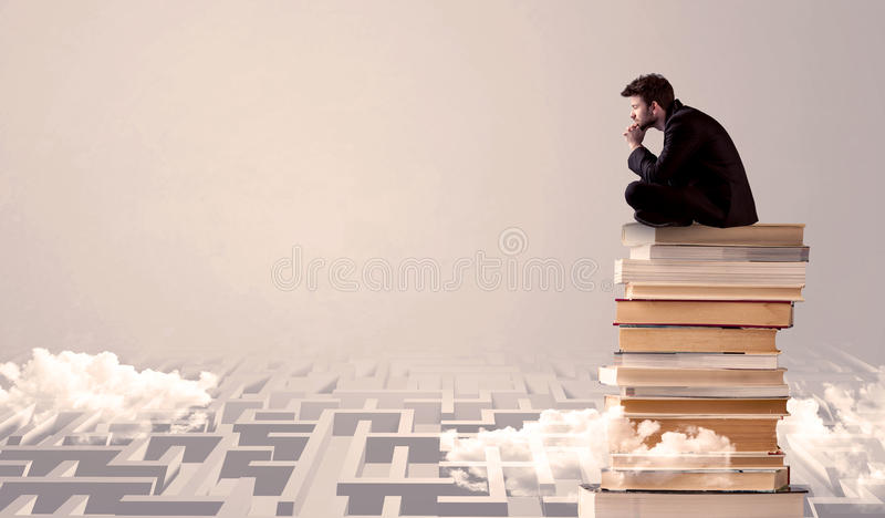Businessman sitting on books in labirynth. A serious businessman in suit sitting on a pile of giant books in front of a grey wall with clouds, labirynth stock photo