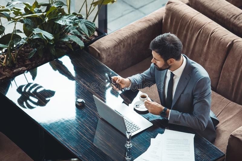 Businessman sitting in a business center restaurant browsing social media top view. Middle-aged man businessman sitting in a business center restaurant browsing royalty free stock image