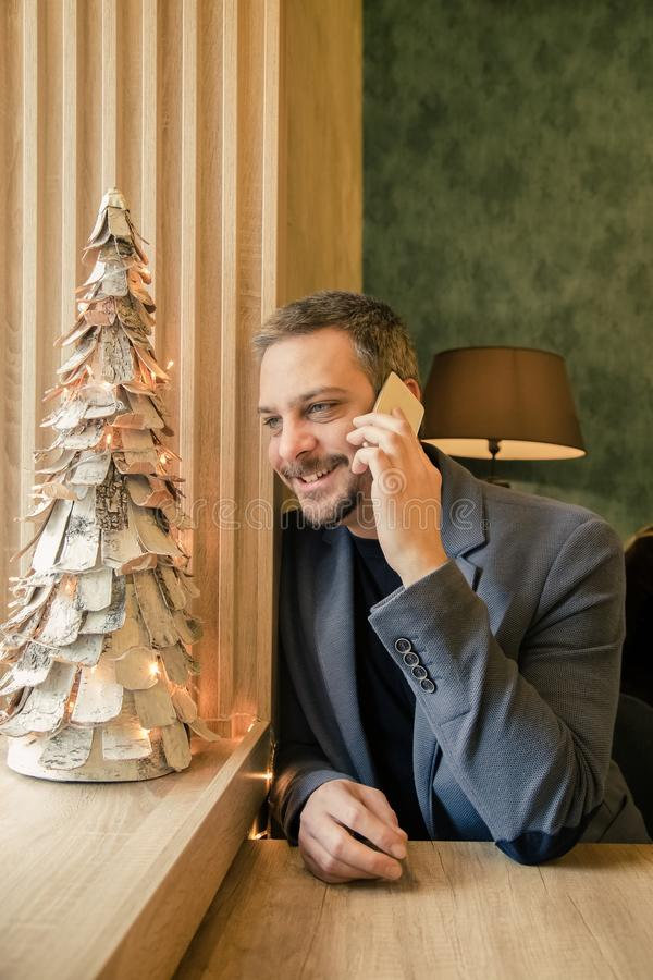 Businessman sitting in cafe and talking on mobile phone, Christmas decoration. stock image