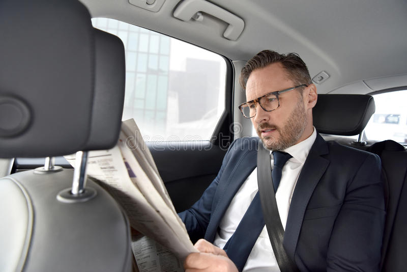 Businessman sitting in car reading newspaper royalty free stock photos