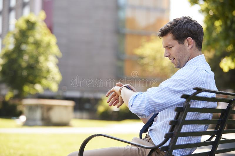 Businessman Sitting In City Park Looking At Smart Watch royalty free stock images