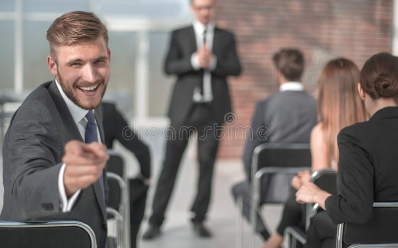 Businessman sitting in the conference room, pointing at you royalty free stock images
