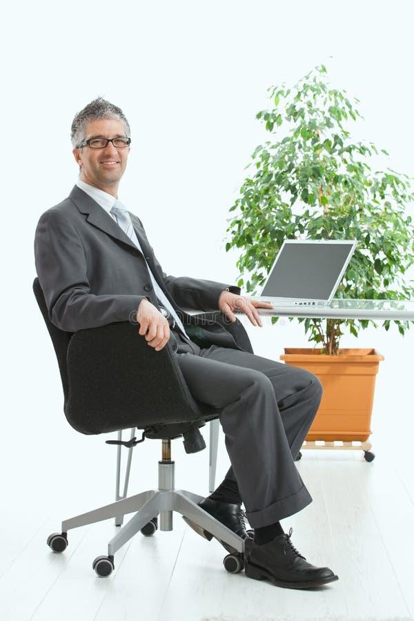Download Businessman Sitting At Desk Stock Photo - Image: 11101776
