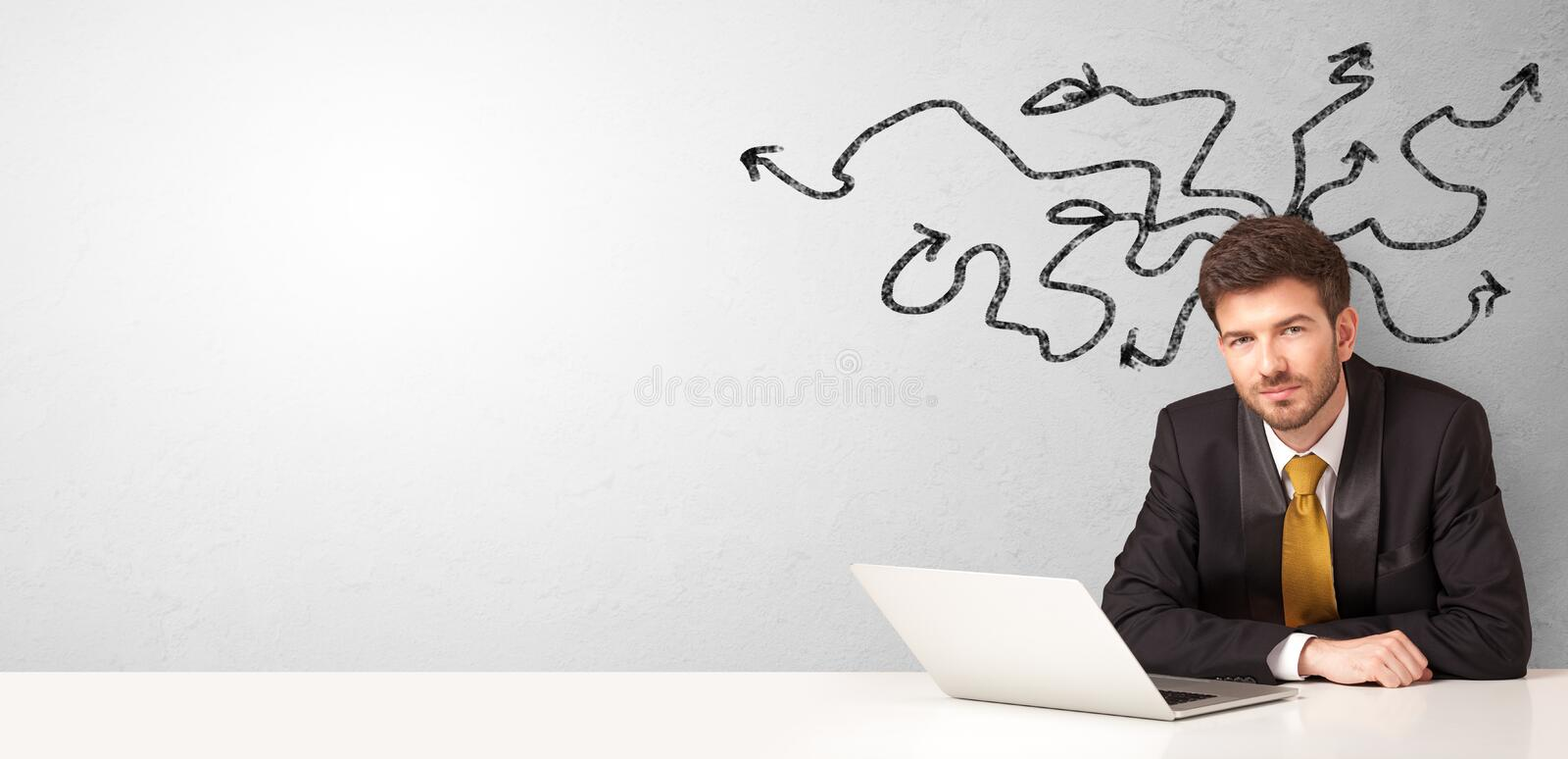 Businessman sitting at desk with arrows around stock image