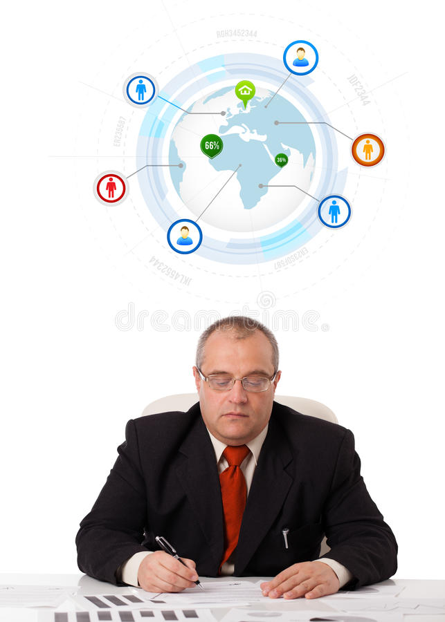 Download Businessman Sitting At Desk With A Globe And Social Icons Stock Photo - Image: 28805290