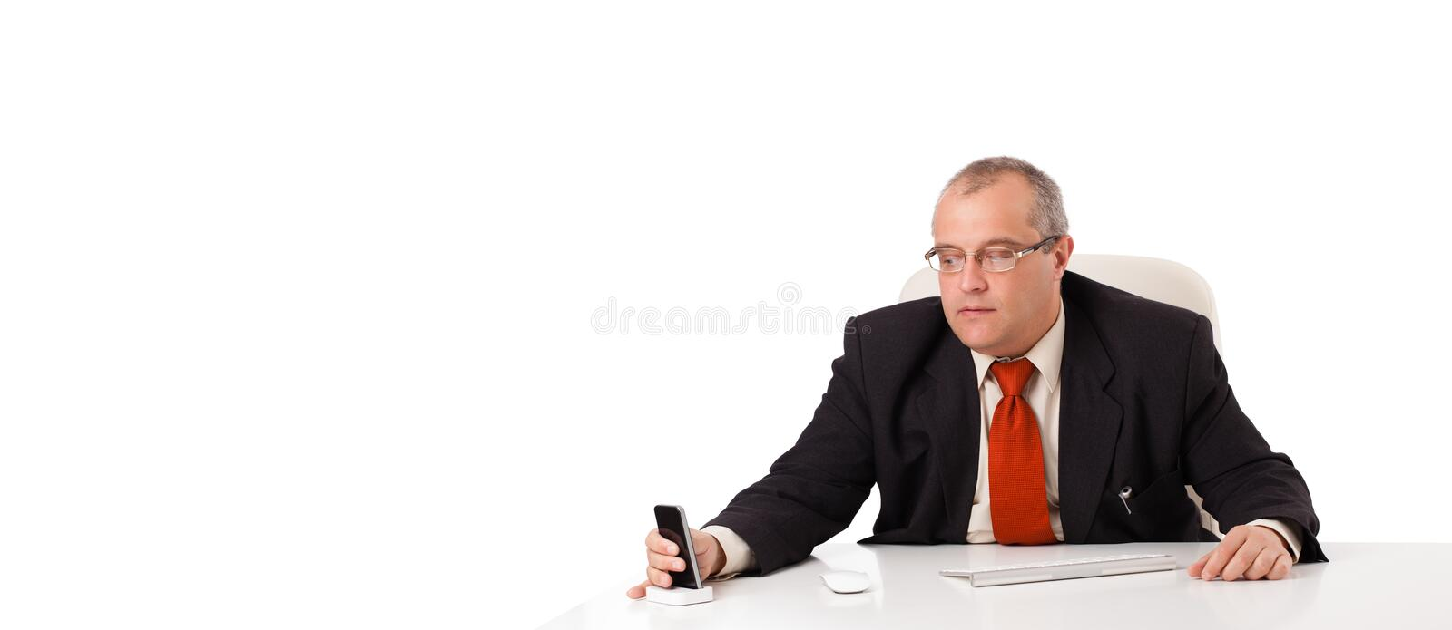 Businessman sitting at desk and holding a mobilephone with copys pace. Isolated on white royalty free stock photos
