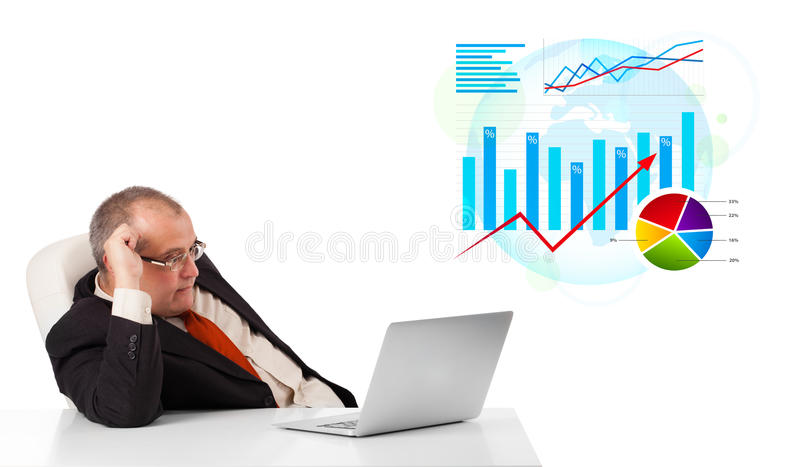 Businessman sitting at desk with laptop and statistics
