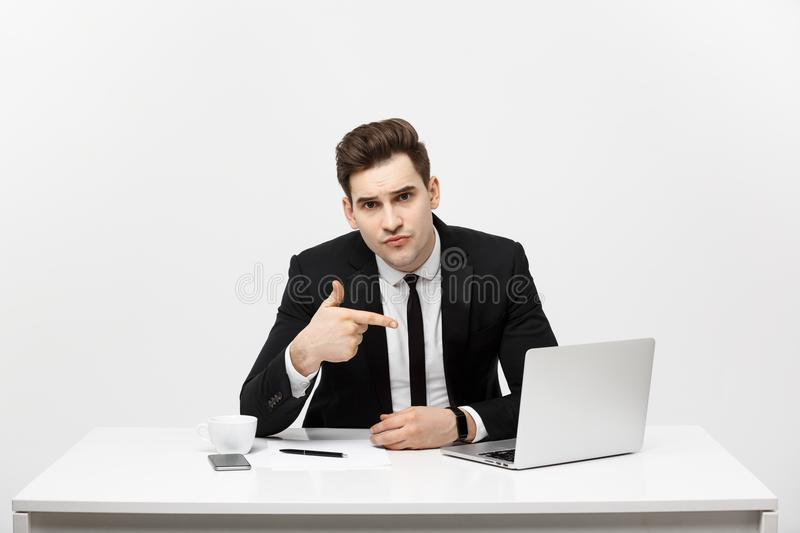 Businessman sitting at desk point finger at isolated laptop screen , handsome young business man looking at camera, over royalty free stock image