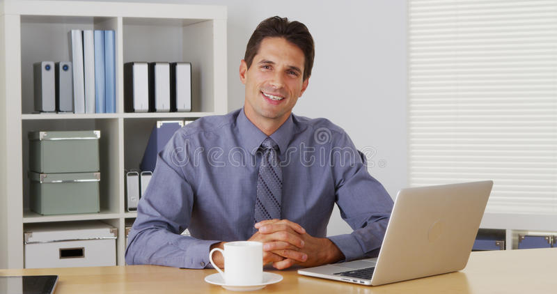 Businessman sitting at desk and talking to camera with laptop. In the office stock photos