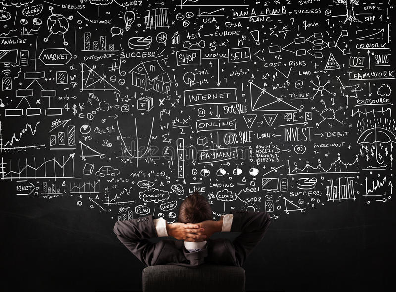 Businessman sitting in front of a blackboard with charts stock photos