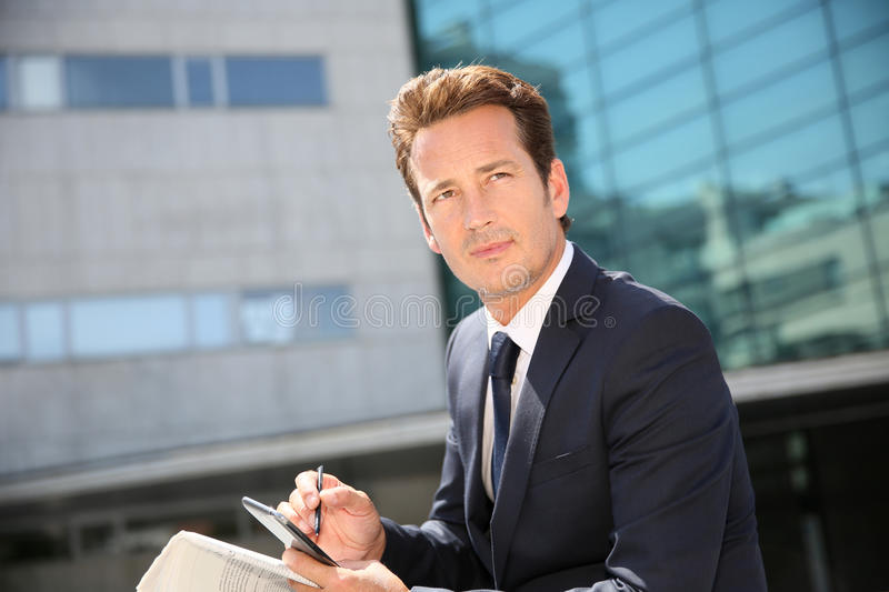 Businessman sitting in front of office building royalty free stock photo