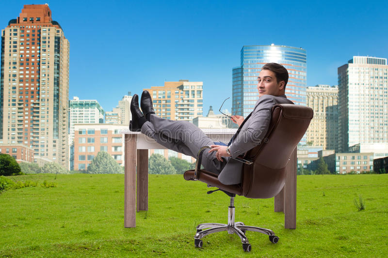 The businessman sitting on grass with city view stock image