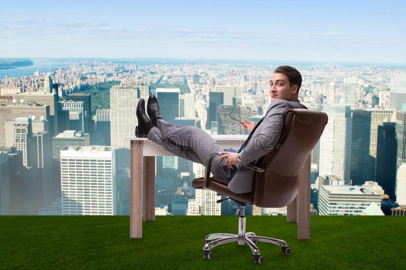 The businessman sitting on grass with city view stock photo