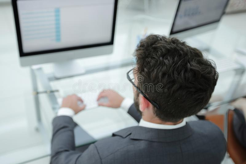 Businessman sitting at his desk and making a financial report. royalty free stock images