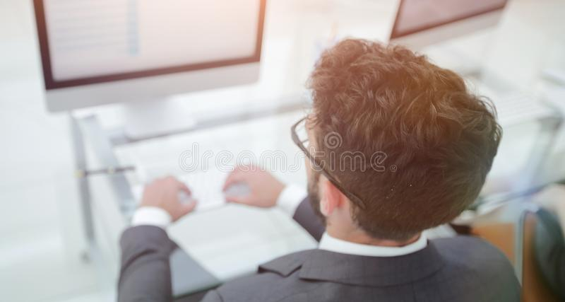 Businessman sitting at his desk and making a financial report. royalty free stock image