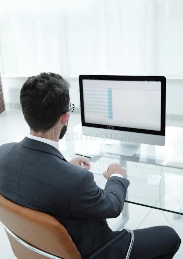 Businessman sitting at his desk and making a financial report. stock photos