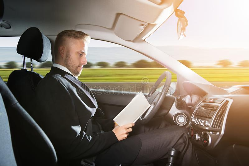 Businessman Sitting Inside Self Driving Car. Young Businessman Sitting Inside Self Driving Car And Reading Book royalty free stock images