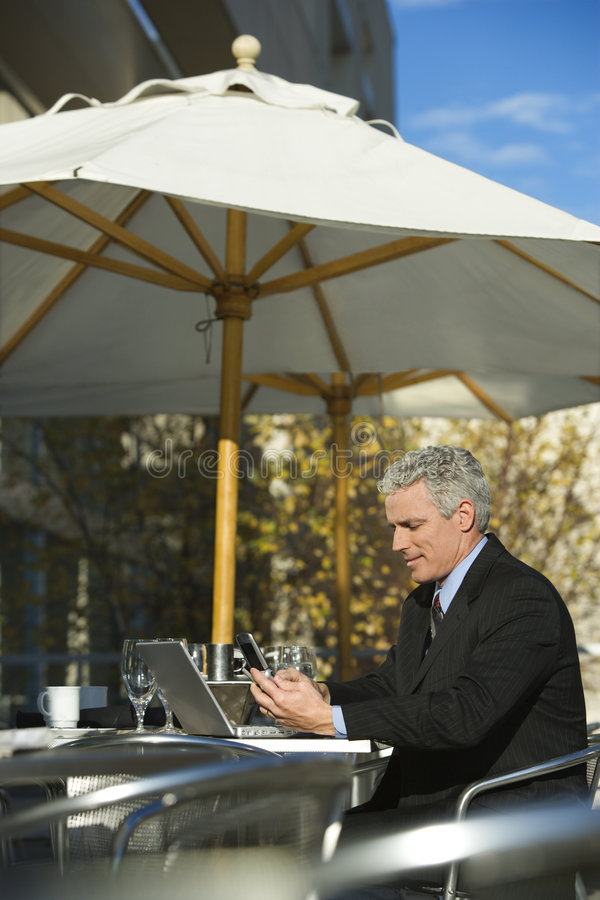 Businessman sitting with laptop and dialing cellphone. royalty free stock photography