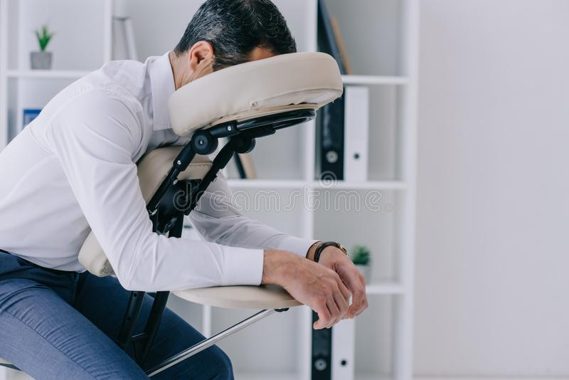 businessman sitting in massage chair royalty free stock photo
