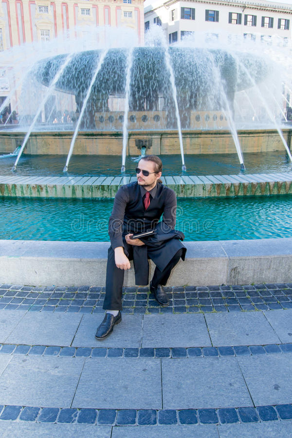 Businessman sitting near a fountain stock photos