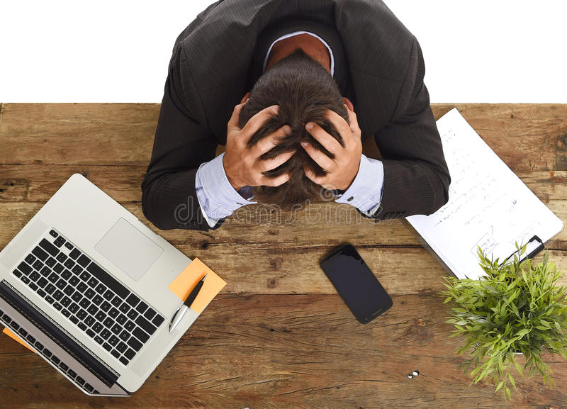 Businessman sitting at office desk with hands on his head crying devastated and frustrated. Desperate stressed businessman sitting at office laptop computer desk royalty free stock photo