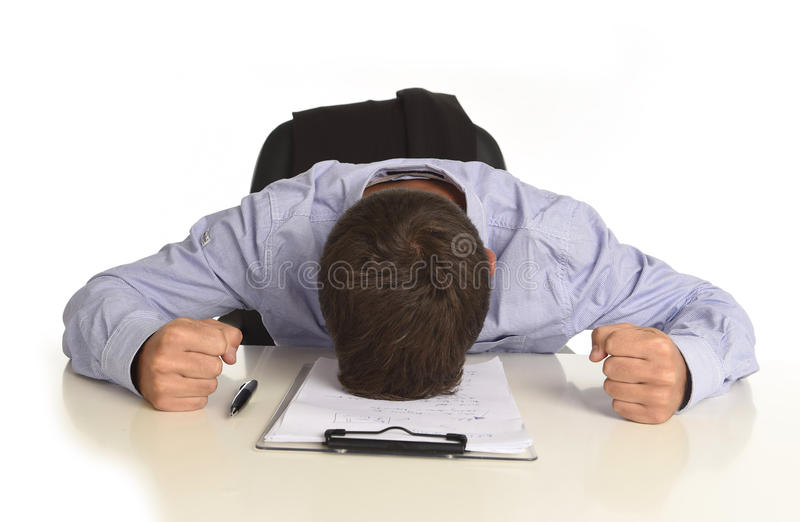 Businessman sitting at office desk with hands on his head crying devastated and frustrated. Desperate stressed businessman sitting at office desk with hands on royalty free stock image