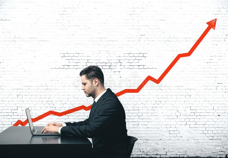 Businessman sitting in office. And drawing red graph of growth on wall stock images