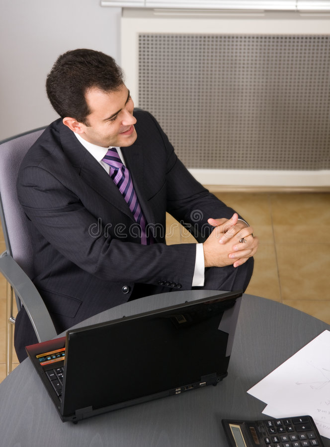 Businessman sitting in office with laptop stock photo