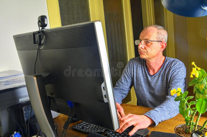 Businessman sitting in an office at the . Middle aged man with glasses sitting at desk. Mature man using mobile phone stock photos