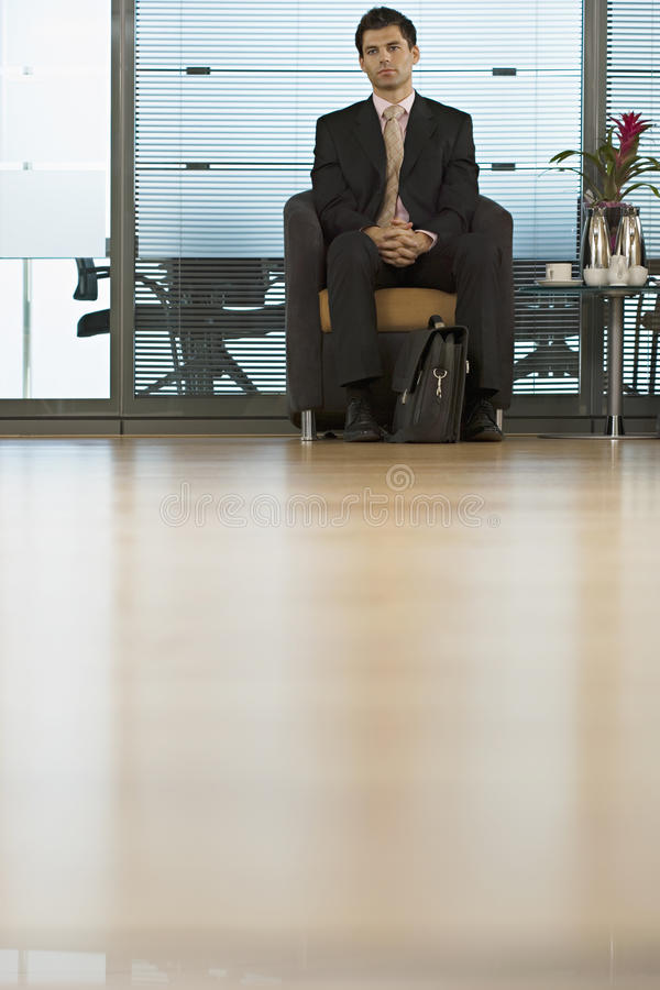 Businessman sitting in office reception area, waiting patiently, front view, surface level royalty free stock images