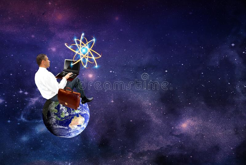 Businessman sitting on a planet Earth with laptop stock images