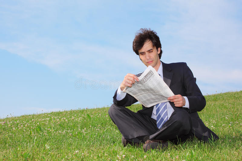 Businessman Sitting And Reading Newspaper Royalty Free Stock Photos
