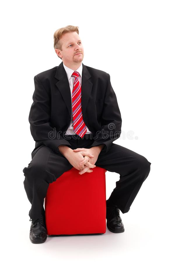 Businessman Sitting On Red Tabouret Stock Photography