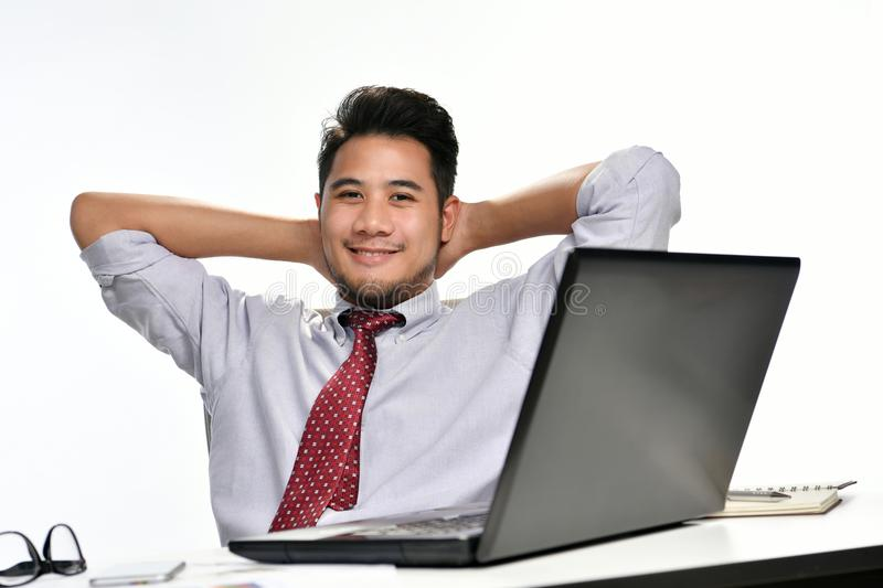 Businessman sitting in relaxed posture after having work done easily. Young businessman sitting in relaxed posture after having work done easily royalty free stock photos