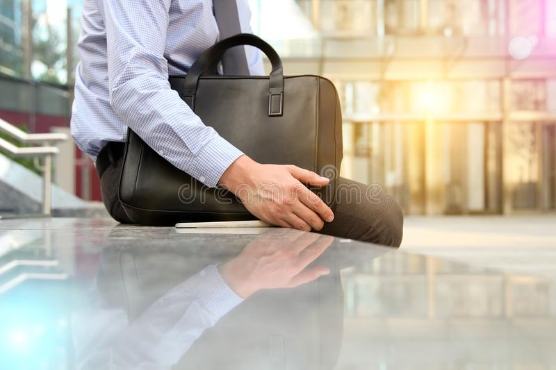 Businessman sitting / resting after working day and holding a leather briefcase in his hand.  stock photo