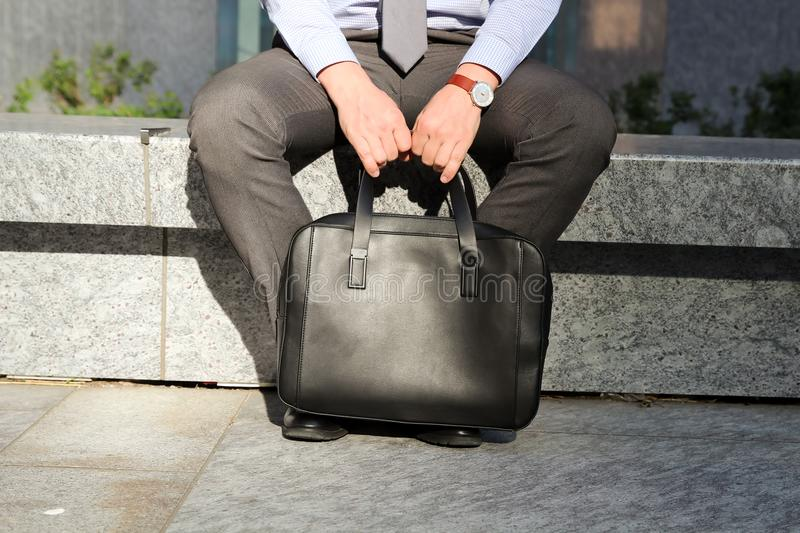 Businessman sitting / resting after working day and holding a leather briefcase in his hand. Businessman sitting / resting after working day and holding a royalty free stock photography