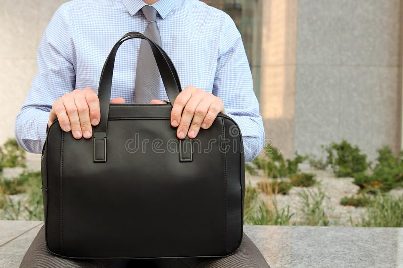 Businessman sitting / resting after working day and holding a leather briefcase in his hand.  stock photos