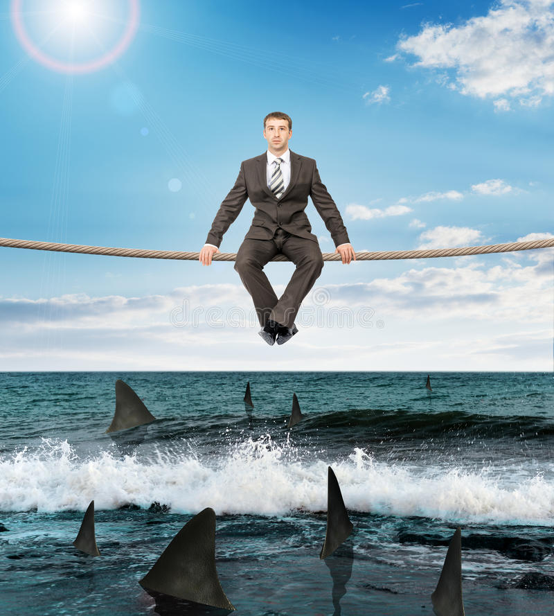 Businessman sitting on rope royalty free stock photography