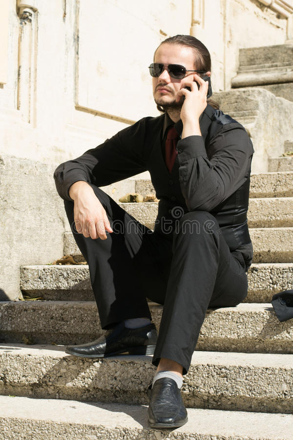 Businessman sitting on stairs and talking on the phone stock image