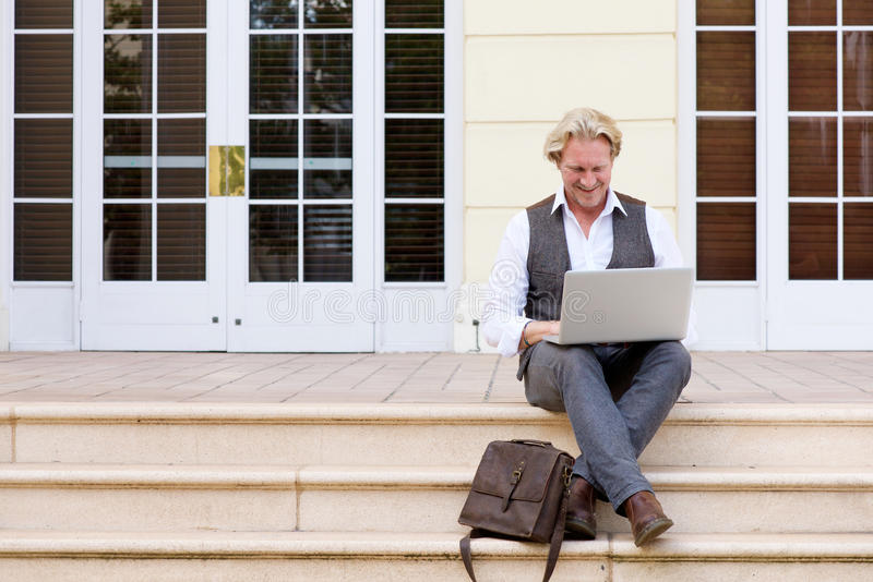 Businessman sitting on steps using laptop computer royalty free stock images