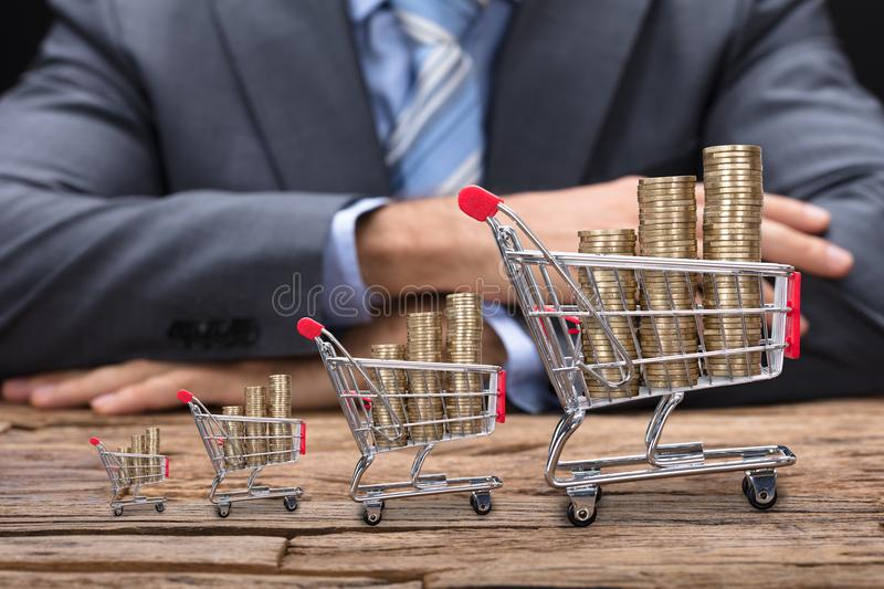 Businessman Sitting At Table With Coins In Shopping Carts stock image
