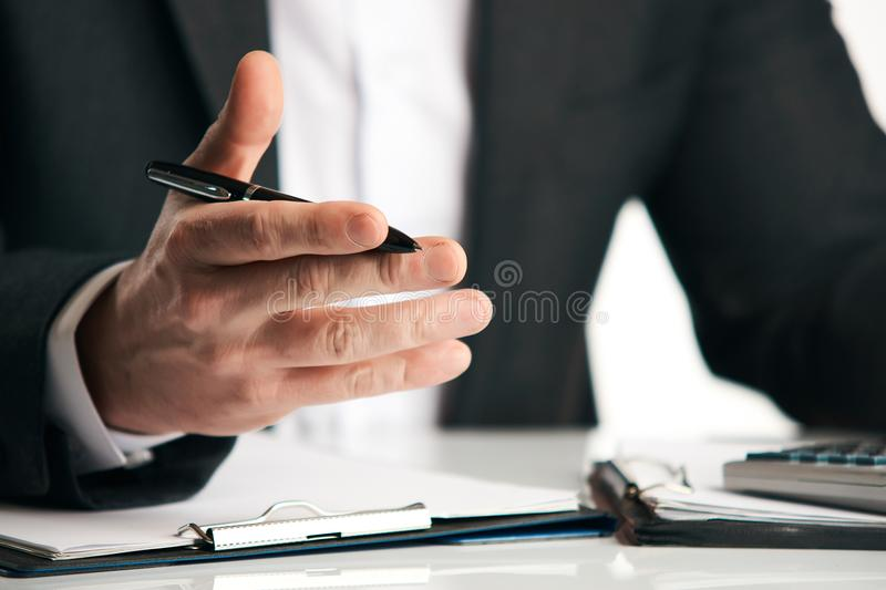 Businessman sitting at the table and explaining something royalty free stock image