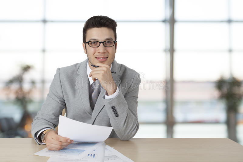 Businessman sitting table and holding document. In office stock image