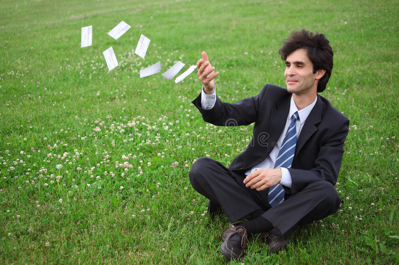Businessman sitting and throwing paper cards. Businessman sitting on the meadow and throwing paper cards royalty free stock photography