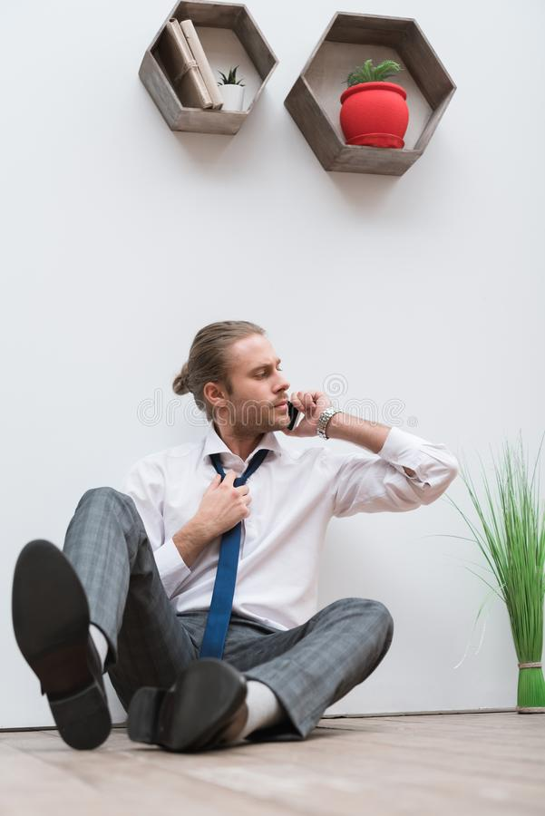 Businessman sitting on a wooden floor, talking by smartphone stock photography