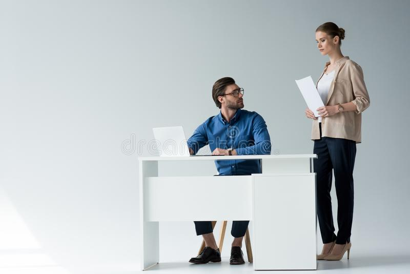 businessman sitting at workplace while his colleague standing with documents behind him royalty free stock image